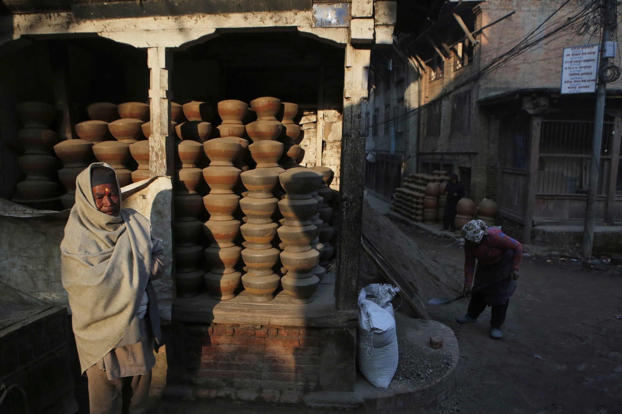 Nepalese Prajapati potter stands beside clay pots neatly stacked up in the ancient Nepali town of Thimi.  (AP Photo)