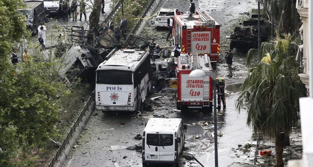 Police officers inspecting the area after a bomb attack yesterday on a police bus, killing 12 and wounding 42 in Istanbul's Vezneciler district.