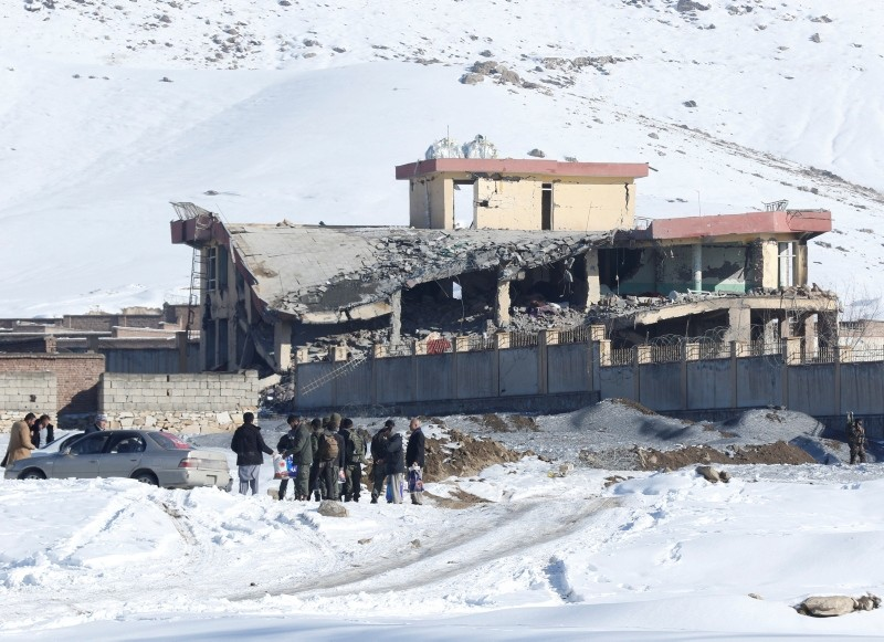 Afghan men stand in front of a collapsed building of a military base after a car bomb attack in Maidan Wardak, Afghanistan, Jan. 21, 2019. (Reuters Photo)