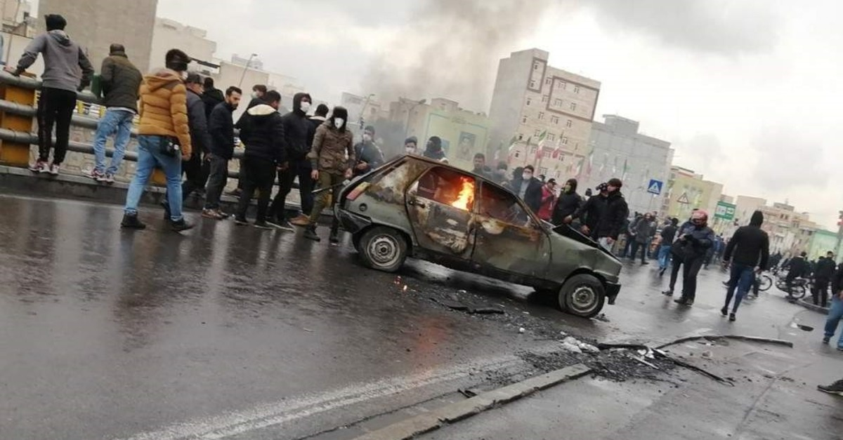 Iranian protesters stand around a vehicle set ablaze during clashes following a fuel price increase in Tehran, Iran, Nov. 16, 2019. (EPA)