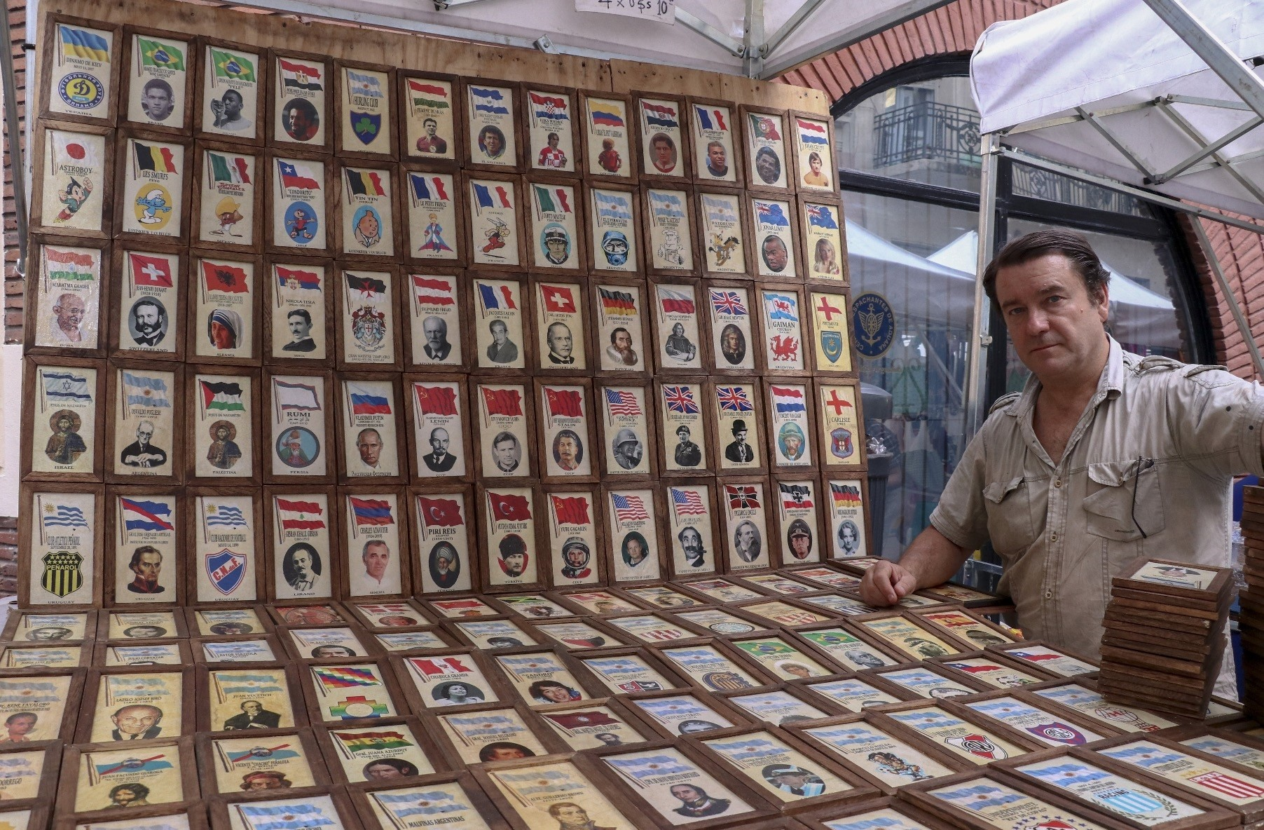 A seller beside his booth where he displays old photographs of influential people and various flags.