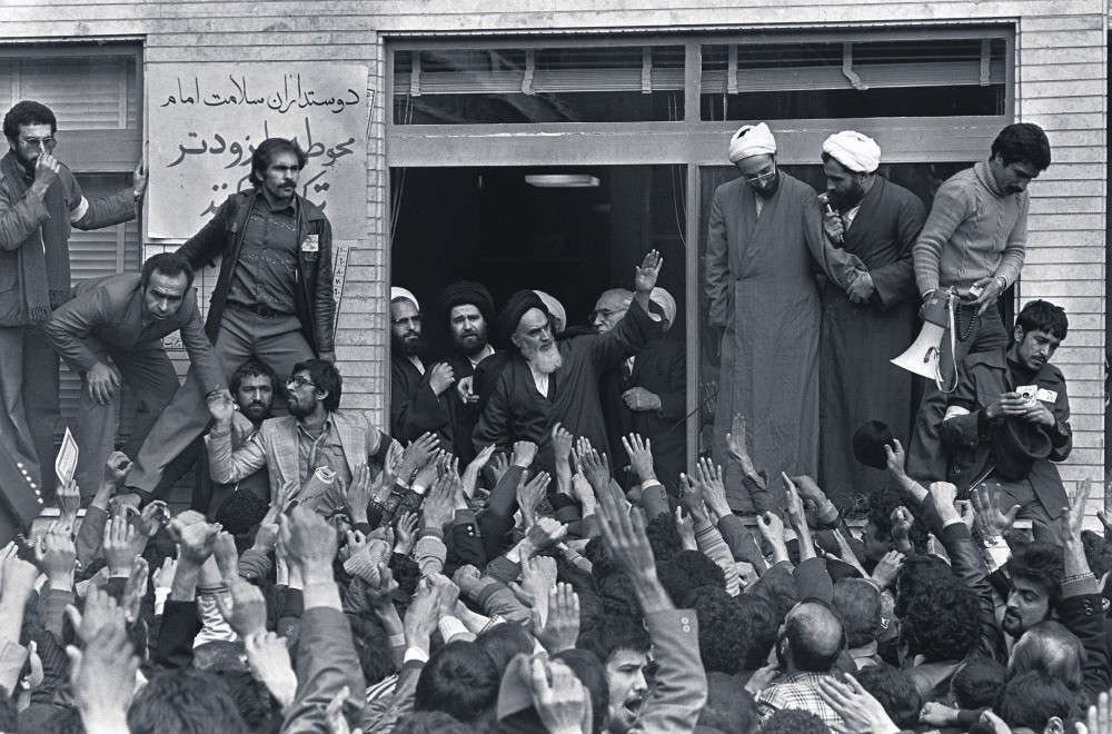 Ayatollah Ruhollah Khomeini waves to his followers on the balcony of his headquarters in Tehran following his arrival in the country as part of a revolution against the Iranian government, Feb. 1, 1979.