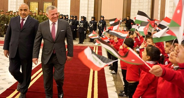 Children wave Iraqi and Jordanian national flags as Iraqi Prime Minister Adel Abdel Mahdi (L) welcomes Jordan's King Abdullah II in the Iraqi capital Baghdad on Jan. 14, 2019. (Jordanian Royal Palace / AFP)