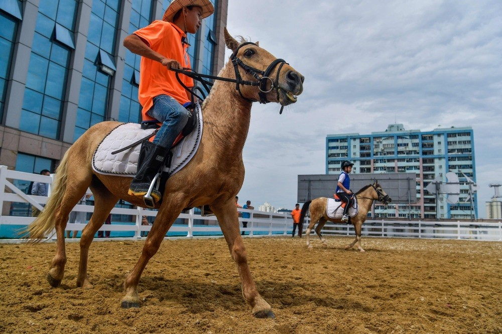 A coach teaches horseback riding on a field built on the roof top of a shopping mall in Haikou in Chinau2019s southern Hainan province.