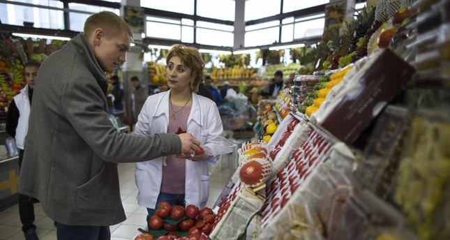 A merchant helps a customer buy tomatoes at Dorogomilovsky food market in Moscow. Since Turkey shot down Russian plane that violated its airspace, Russia has restricted tourism, left Turkish trucks stranded at border and confiscated imports.