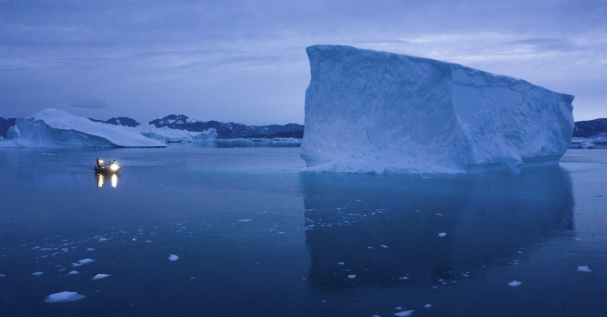 A boat navigates at night next to large icebergs in eastern Greenland, Aug. 15, 2019.