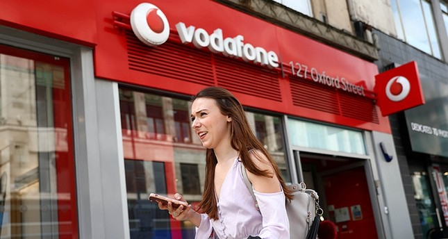 A woman holds a phone as she passes a Vodafone store in London, Britain May 16, 2017. (Reuters Photo)