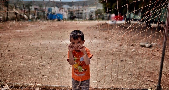 A boy looks from behind a net at the refugee camp of Schisto on June 8. (AFP Photo)