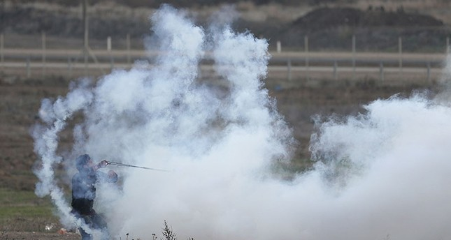 A Palestinian protester throws back a teargas canister that was fired by Israeli soldiers during clashes on the Israeli border with Gaza, Thursday, Dec. 7, 2017 (AP Photo)