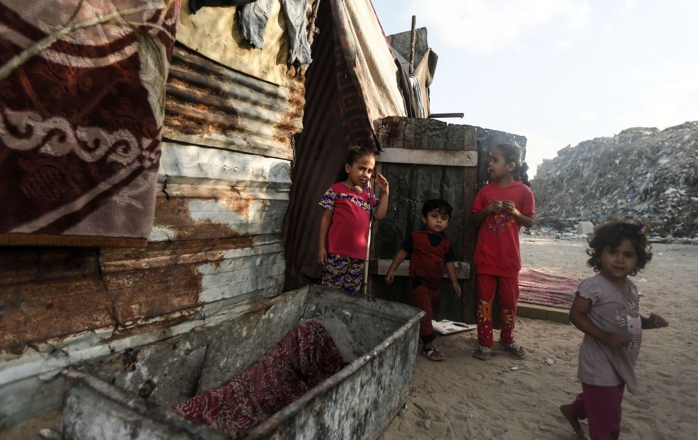 Palestinian children gather in front of a tin house in an impoverished neighborhood of the Khan Younis refugee camp, southern Gaza Strip,  Aug. 25.