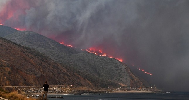 A man watches as the Woolsey Fire reaches the ocean along Pacific Coast Highway Highway 1 near Malibu, California AFP Photo