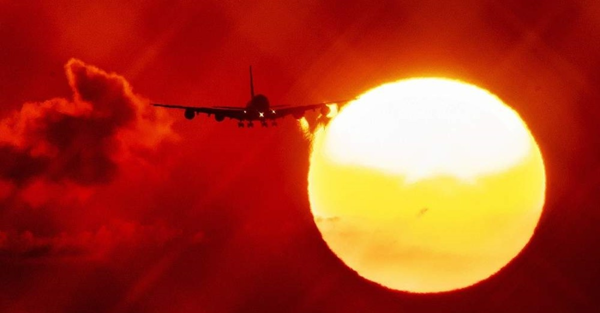 In this Wednesday, Aug. 21, 2019 file photo, an aircraft passes the rising sun as it approaches the airport in Frankfurt, Germany. (AP Photo)