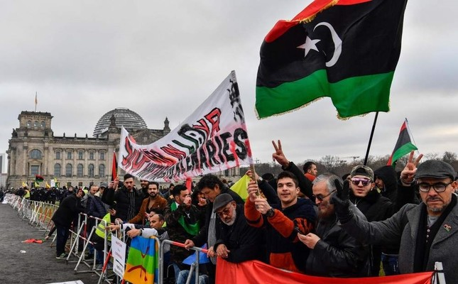 Protesters hold a banner reading Stop war in Libya, Haftar and mercenaries during a protest in front of the Reichstag building during the Peace summit on Libya at the Chancellery in Berlin, Jan.19, 2020.  AFP