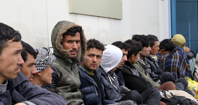 Migrants, including Afghans and Pakistanis, wait outside a police station after they were intercepted in Erzurum, April 3.
