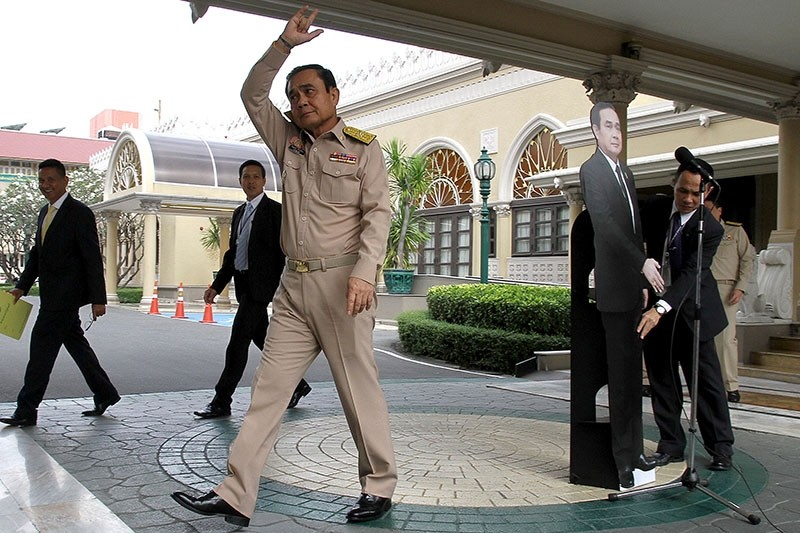 Thailand's Prime Minster Prayuth Chan-ocha waves to reporters next to a cardboard cut-out of himself at the government house in Bangkok, Thailand Jan. 8, 2018.(Dailynews via Reuters)