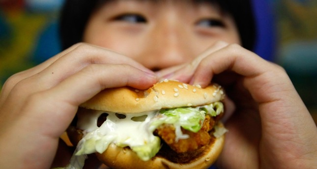 A boy poses with a chicken burger at a fast food outlet in Taipei January 29, 2010. (Reuters Photo)