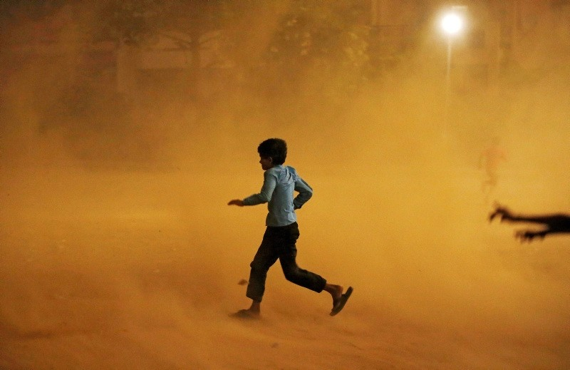 A boy runs for cover during a dust storm in New Delhi, India May 13, 2018 (Reuters Photo)