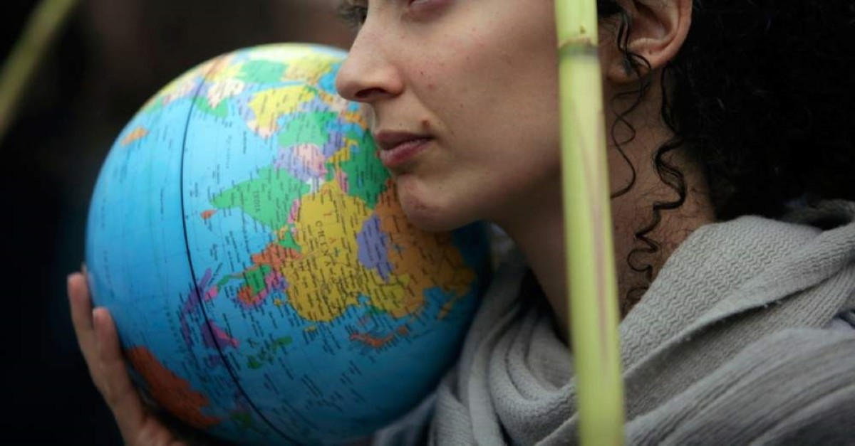 A demonstrator holds a terrestrial globe in Lisbon during a worldwide protest demanding action on climate change, Friday, Nov. 29, 2019. (AP Photo)