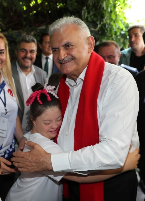 Yıldırım embraces a Turkish child with down syndrome.