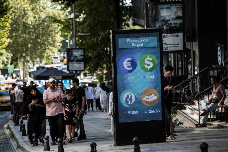 People walk past a digital billboard giving updates on various currencies and the Turkish stock exchange in Istanbul on August 13, 2018. (EPA Photo)