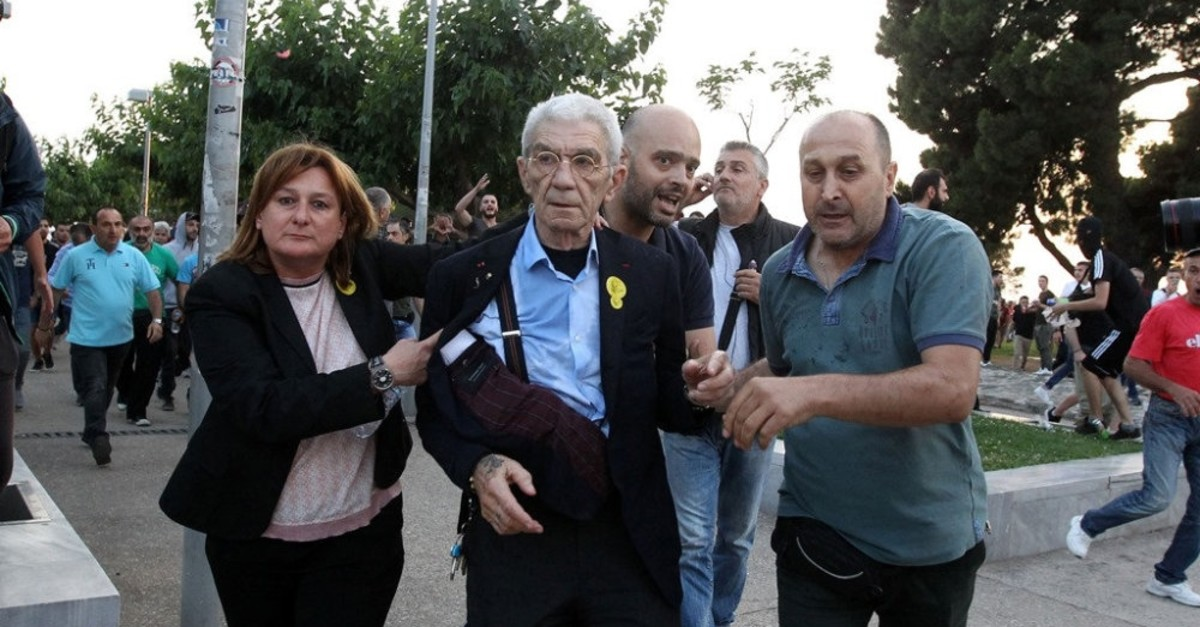 The Mayor of Thessaloniki, Yiannis Boutaris (C), is assisted after being attacked by a mob of far-right extremists during Remembrance Day in the city of Thessaloniki, northern Greece, May 19, 2018.