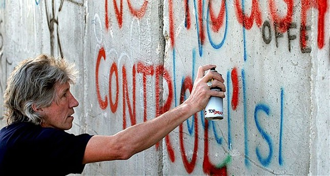 British rock musician and Pink Floyd co-founder Roger Waters spray-paints the words No Thought Control on a section of what Palestinians call Israel's apartheid wall in the West Bank town of Bethlehem, June 21, 2006. (AP Photo)