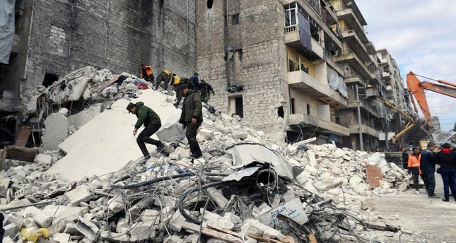 In this photo released by SANA, people inspect a destroyed building where the five-story building collapsed early Saturday. (SANAA Photo via AP)