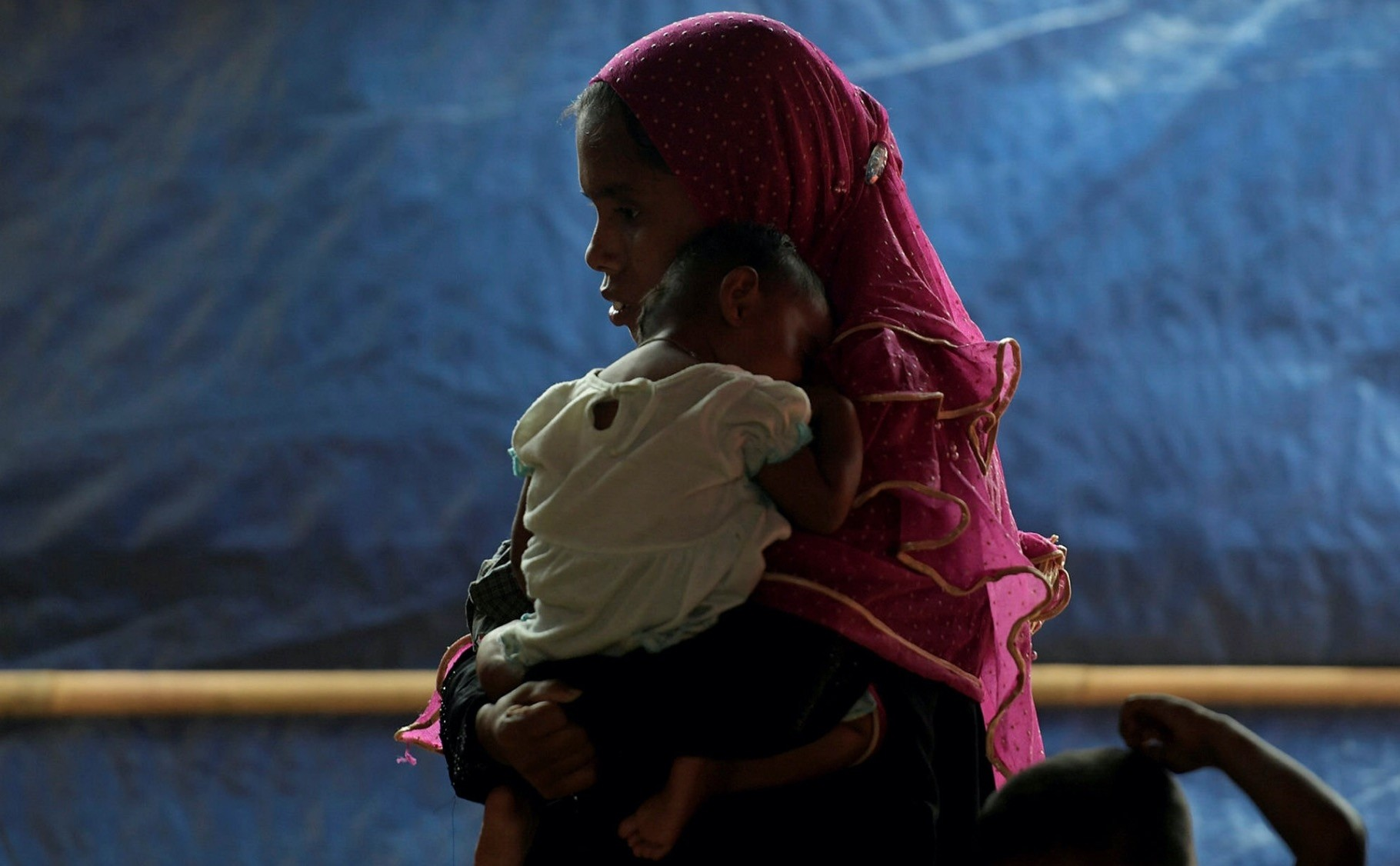 A Rohingya woman visits a health clinic with her baby at the Balukhali Refugee Camp.
