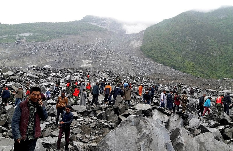 People search for survivors at the site of a landslide that destroyed some 40 households, where more than 140 people are feared to be buried. (AFP Photo)