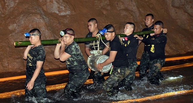 An undated photo released by Royal Thai Army on July 2, 2018 shows Thai soldiers carrying equipment inside the flooded cave complex during a rescue operation for a missing youth soccer team and their coach at Tham Luang cave. (EPA Photo)