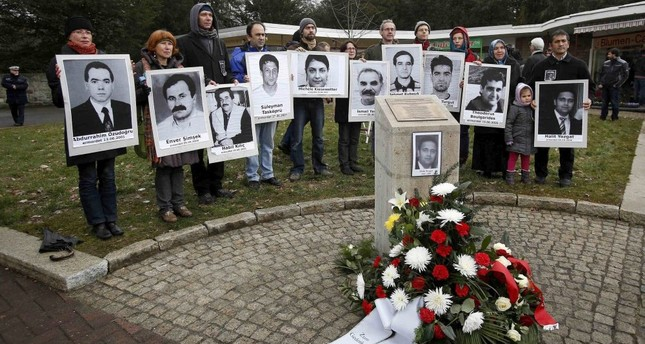 People carrying photos of NSU victims stand around a monument erected in memory of Halit Yozgat, one of the victims, in Germany's Kassel. Amnesty says institutional racism led police to downplay racist motives behind the murders.