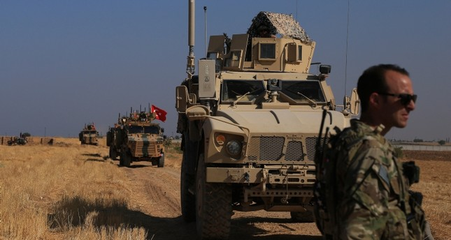 Turkish and American armored vehicles patrol as they conduct joint ground patrol in the safe zone on the Syrian side of the border with Turkey (AP Photo)