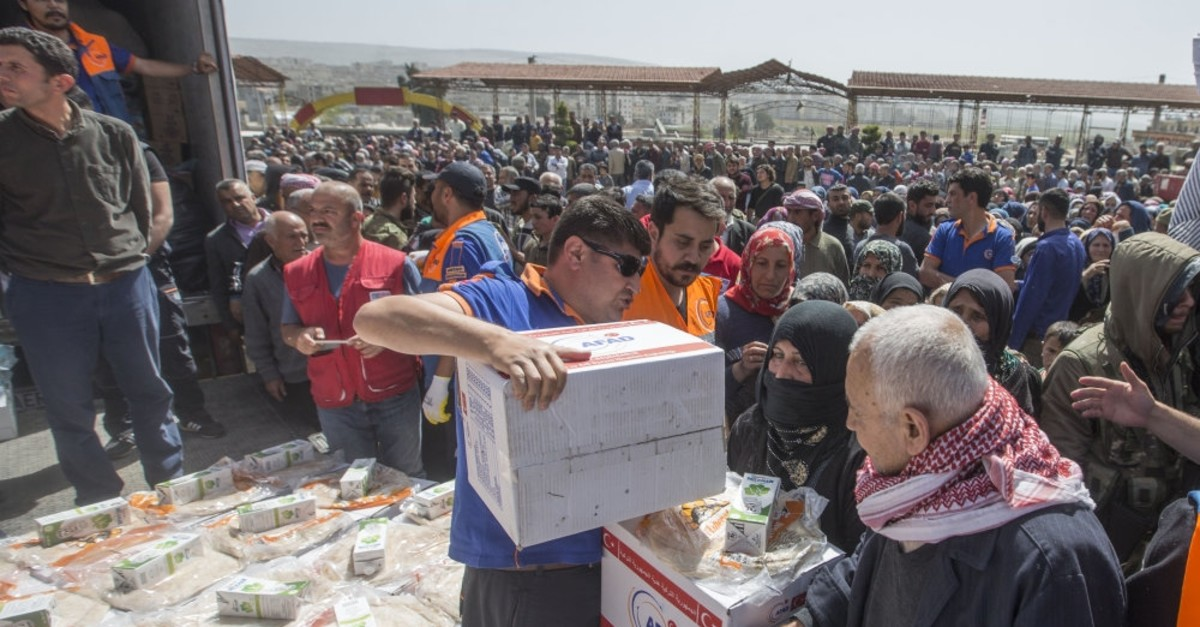 Aid workers of Turkey's Disaster and Emergency Management Authority (AFAD) deliver food packages to families in Afrin, Syria, March 29, 2018.