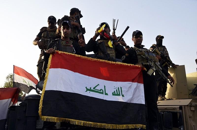 Iraqi soldiers hold up the Iraqi national flag in Mosul, Iraq, July 10, 2017. (EPA Photo)