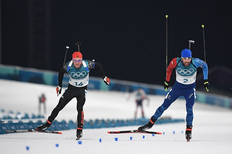 Simon Schempp, of Germany, left, and Martin Fourcade, of France, right, cross the finish line during the men's 15-kilometer mass start biathlon at the 2018 Winter Olympics in Pyeongchang, South Korea, Sunday, Feb. 18, 2018. (AP Photo)