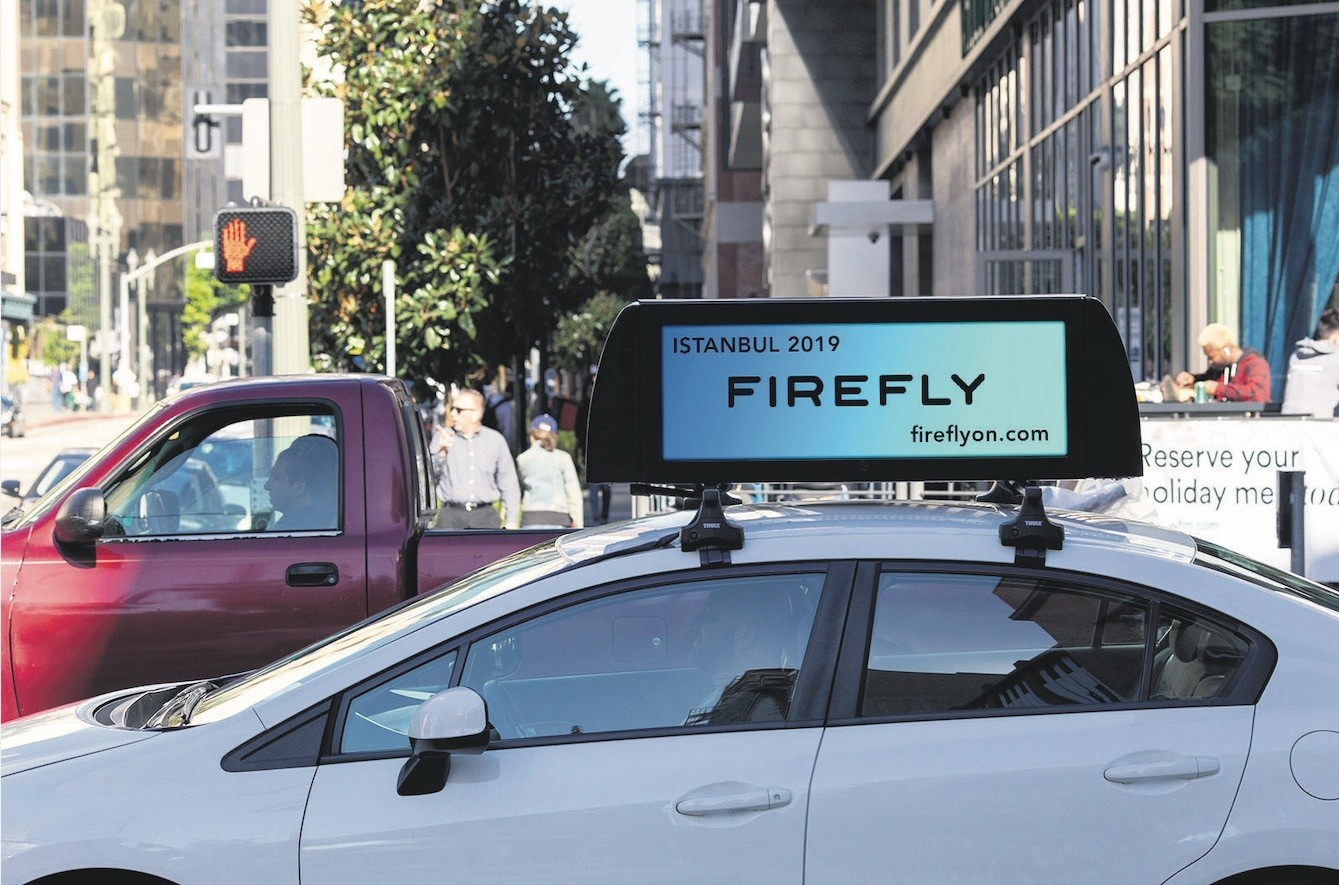 An Uber vehicle carries a FireFly smart advertisement board.