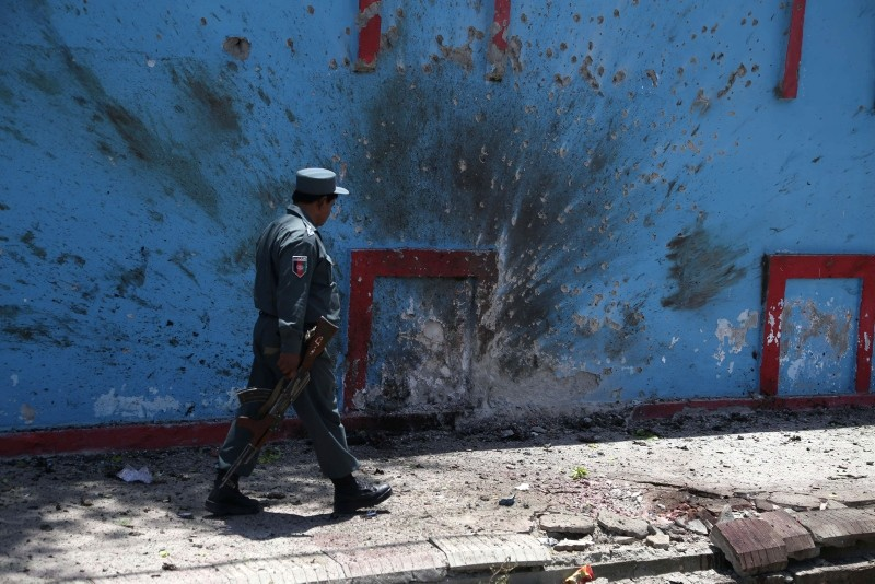 An Afghan Policeman inspects the scene of a suicide bomb attack in Jalalabad, Afghanistan, 11 June 2018. (EPA Photo)
