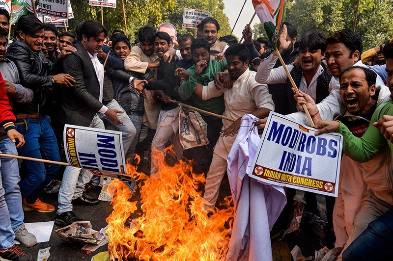 Indian supporters of the Congress Party shout slogans as they burn effigy of billionaire jeweller Nirav Modi in New Delhi on Feb. 16, 2018. (AFP Photo)