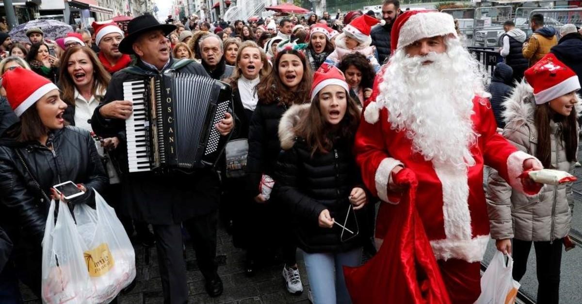 Zografyon Greek High School principal Yani Demircioglu, accompanied by schoolchildren and members of the Greek Orthodox community, plays the accordion during Christmas celebrations on main ?stiklal Street, Istanbul, Dec. 24, 2019. (Reuters Photo)