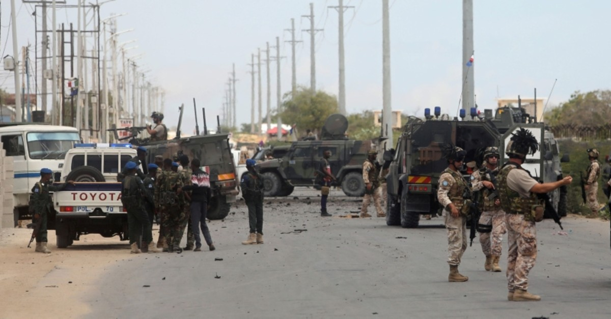 Italian and Somali security forces are seen near armoured vehicles at the scene of an attack on an Italian military convoy in Mogadishu, Somalia Sept. 30, 2019. (Reuters Photo)