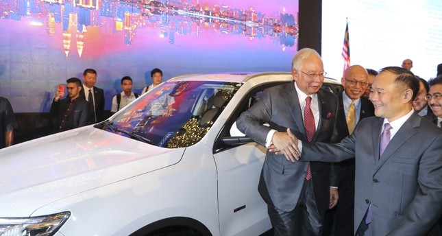 Malaysian Prime Minister Najib Razak shakes hand with Zhejiang Geely CEO Li Shufu, right, after a signing ceremony for Proton and Geely in Kuala Lumpur, Malaysia.