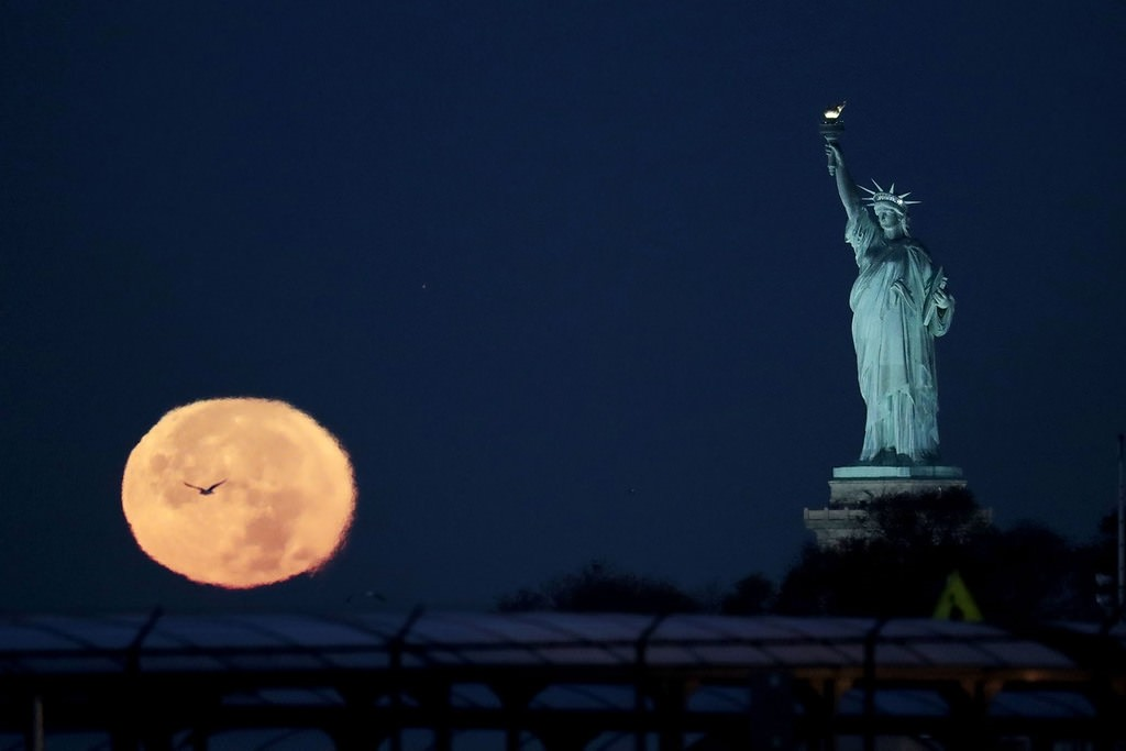 The supermoon appears near the Statue of Liberty, Monday, Nov. 14, 2016, in New York. AP Photo
