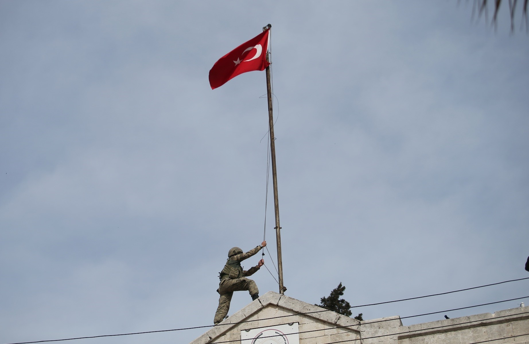 A Turkish soldier hoists the Turkish national flag on a building after after it was liberated from YPG terrorists as part of Operation Olive Branch, March 18.