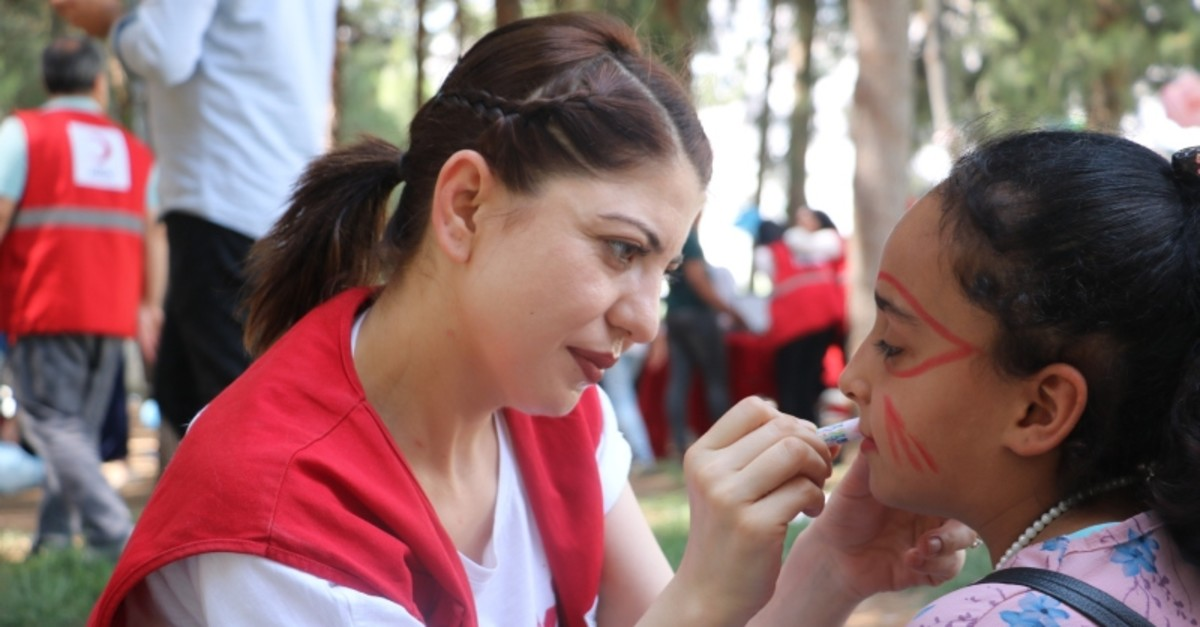 A Turkish Red Crescent volunteer paints a refugee girls face during World Refugee Day events in southeastern Gaziantep province, June 21, 2019. (IHA Photo)