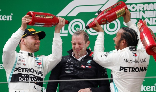 Mercedes driver Lewis Hamilton and teammate Valtteri Bottas pour champagne over team engineer Marcus Dudley during the award ceremony for the Chinese Formula One Grand Prix at the Shanghai International Circuit in Shanghai, April 14, 2019. (AP Photo)