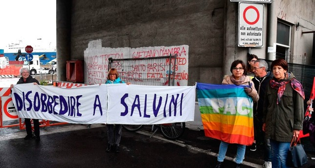 Activists holds up a sign with writing reading in Italian Disobey Salvinias they demonstrate after Saudi Arabian freighter Bahri Yambu docked in Genoa's port, Italy, Monday, May 20, 2019 (AP Photo)