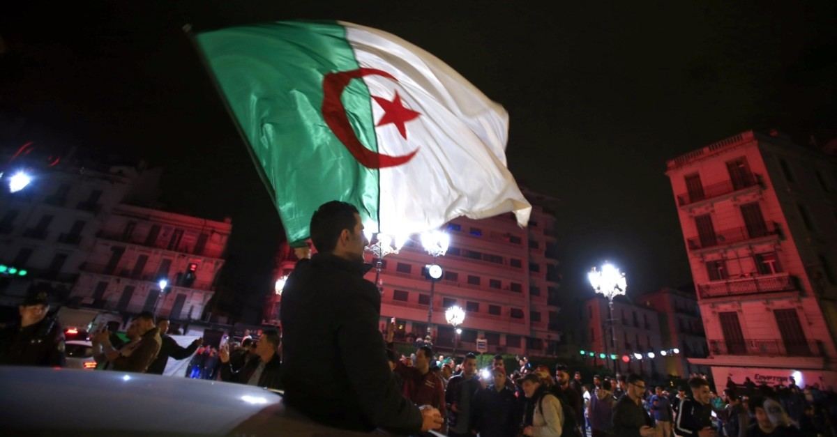 Algerian people, waving their national flags, celebrate in the streets of Algiers after President Abdelaziz Bouteflika announced that he is delaying the April 18 election and won't seek another term, March 11, 2019.