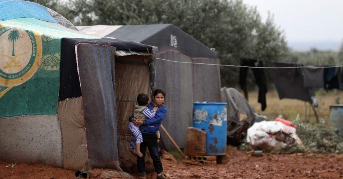 Syrian children, who fled air strikes in their hometown, are pictured near tents at an informal camp for displaced people where they live with their families in Idlib, Jan. 7, 2020.  (AFP PHOTO)