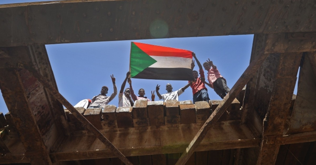 Sudanese protesters wave a national flag near the military headquarters in the capital Khartoum on May 17, 2019, during an ongoing sit-in demanding a civilian-led government transition. (AFP Photo)