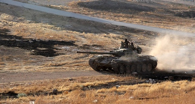 Opposition fighters drive a tank in the Al-Huweiz area on southern outskirts of Aleppo as they battle to break the government siege on the northern Syrian city on August 2, 2016. (AFP Photo)